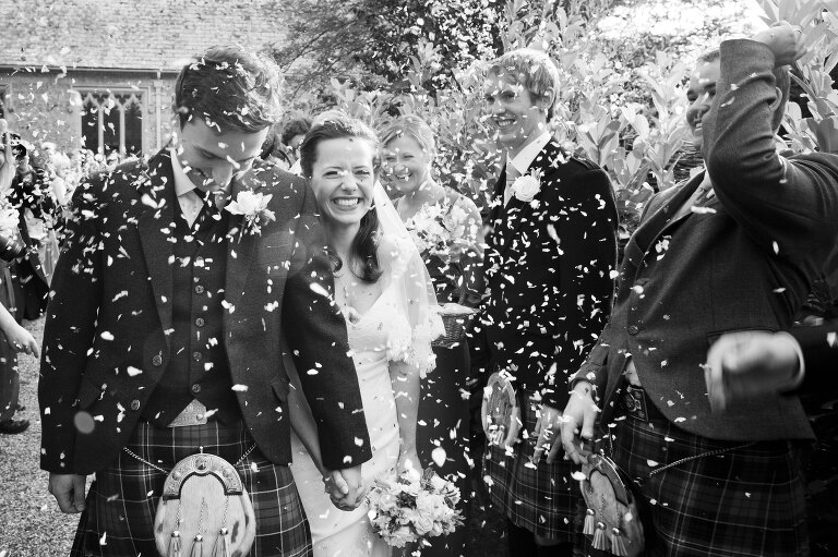 Reportage Wedding Photograph of Bride & Groom having Confetti Thrown