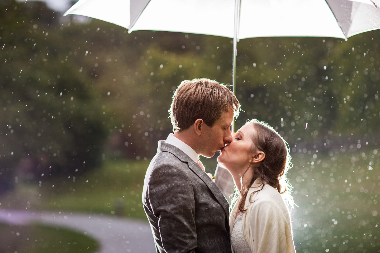 Rainy Wedding Photography - Bride & Groom Kissing under an umbrella