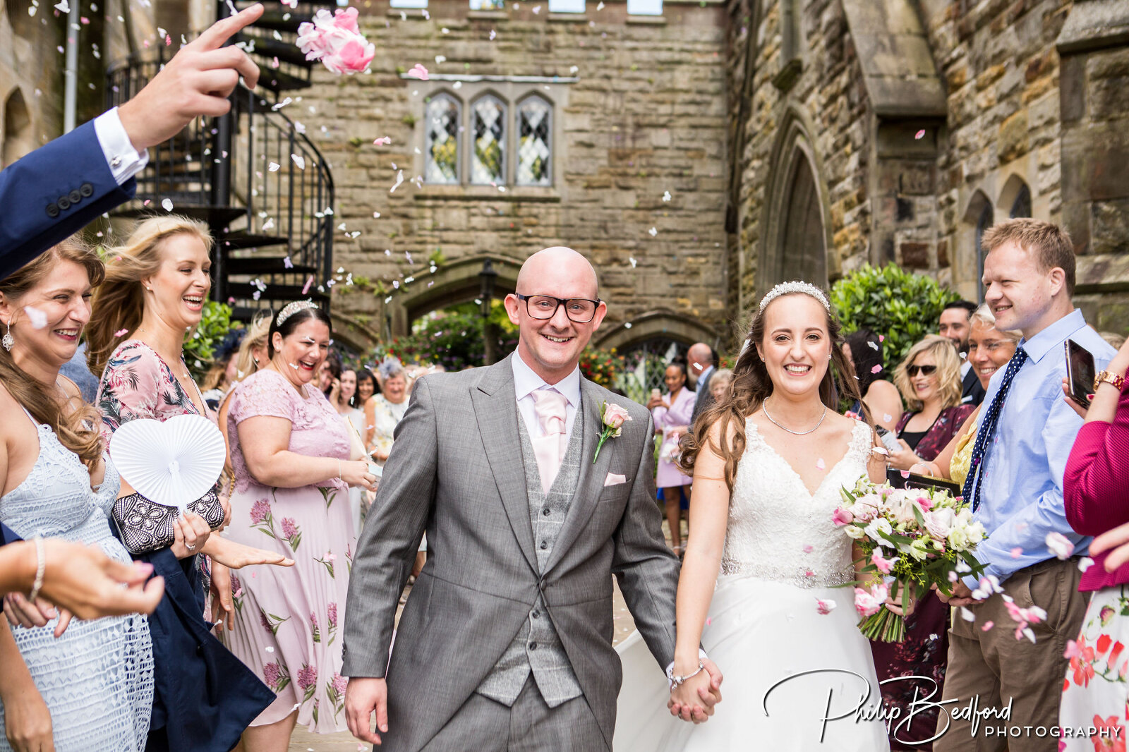 Relaxed Wedding Photograph of Bride & Groom Walking through hotel Grounds throwing Confetti